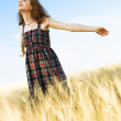 Beautfiul woman in checkered dress in a field — Stock Photo #5727299