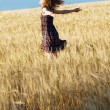 Beautiful woman in checkered dress in a field - Stock Photo