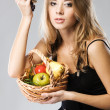 Pretty woman with a basket of fruit — Stock Photo #5727469