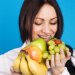 Beautiful young girl with a bunch of fruits — Stock Photo