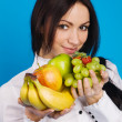 Beautiful young girl with a bunch of fruits — Stock Photo #5728055