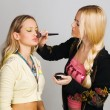 Professional beautician applying makeup — Stock Photo
