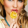 Stock Photo: Fashionable young woman holding a candy