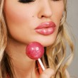 Young woman with vibrant makeup holding a lollipop — Stock Photo