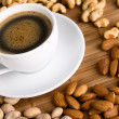 Stock Photo: Coffee with nuts on background