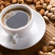 White cup of coffee with lot of nuts — Stock Photo