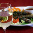 Wineglass with a dish - Stock Photo