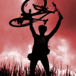 Silhouette of a biker holding his bicycle - Stock Photo