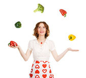 Young beautiful woman juggling with vegetables — Stock Photo