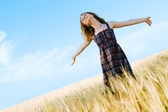 Beautiful woman in checkered dress in a field — Stock Photo