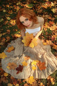 一名年轻女子在黄色叶子的浪漫图片 — 图库照片