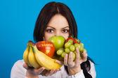 Vacker ung flicka med en massa frukter — Stockfoto
