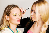 Professional visagiste applying makeup — Stok fotoğraf