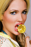 Fashionable young woman holding a candy — Stock Photo