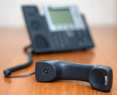 Telephone receiver with phone on background — Stock Photo