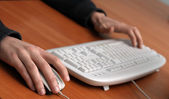 Hands of a man on mouse and keyboard — Stock Photo