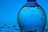 Mineral water bottle on blue background — Stock Photo