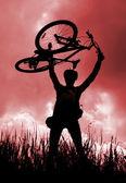 Silhouette d'un motard, tenant son vélo — Photo