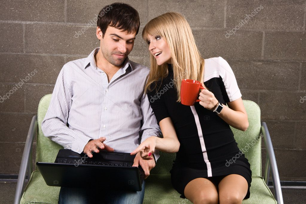Young man and woman sitting with a laptop indoors — Stock Photo #5725900