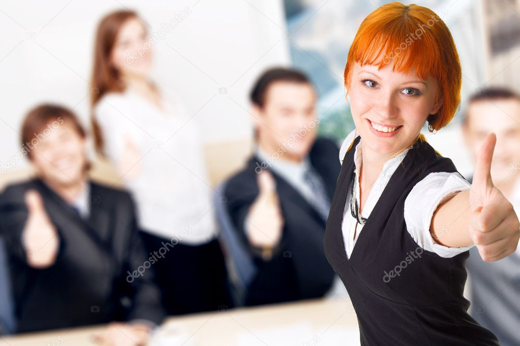 Business showing thumbs up, with pretty redhead lady on foreground  Stock Photo #5726690