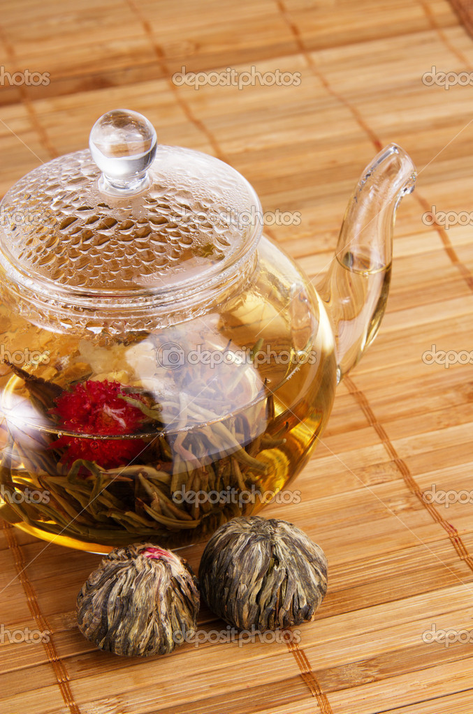 Closeup of glass teapot with fresh tea and dry tea flowers  Stock Photo #5729290
