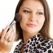Beautiful young woman applying makeup - Stock Photo