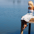 Girl sitting on a pier at the river bank — Stock Photo