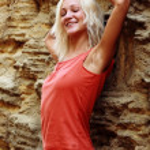 Beautiful girl posing on a stone wall background — Stock Photo
