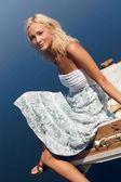 女孩坐在河岸边码头上 — 图库照片