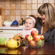 Happy mother with her little daughter having lunch — Stock Photo