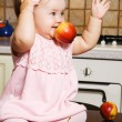 Little girl playing with red apples — Stock fotografie