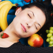 Beautiful young woman with a bunch of fruits — ストック写真