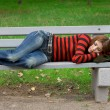 Girl sleeping on a park bench — Stock Photo