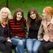Stock Photo: Four girls sitting on a park bench
