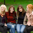 Four girls sitting on a park bench — Stock Photo