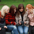 Four girls having fun with a digital camera — Stock Photo