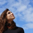 Beautiful young woman looking into the sky — Stock Photo