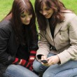 Two young women with a mobile phone — Stock Photo