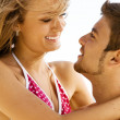 Young cheerful couple having fun on the beach — Stockfoto
