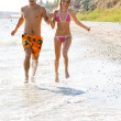 Young couple running along the beach — Stock Photo