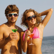 Young couple on the seaside with cocktails — Stock Photo #5758356