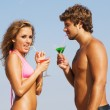 Young couple on the seaside with cocktails — Stock Photo #5758360