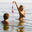 Sexy girl undressing in the water with boyfriend — Stock Photo