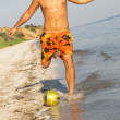 Young man playing football on a sea shore — Stock Photo
