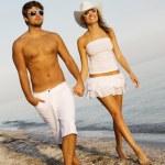 Young elegant couple walking on the seashore — Stock Photo