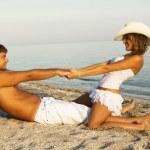 Beautiful young couple having fun on the seashore — Stock Photo