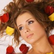 Beautiful young woman lying in rose petals — Stock Photo #5758443