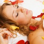 Beautiful young woman lying in rose petals — Stock Photo #5758445