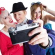 Joyful teenage friends with photo camera — Stock Photo