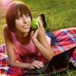 härlig tjej med laptop i parken — Stockfoto
